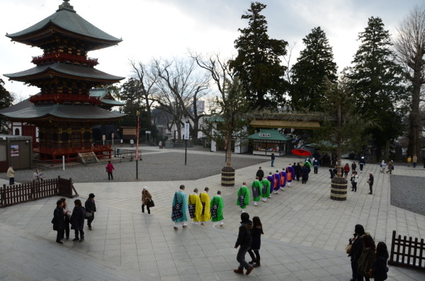 Průvod mnichů na nádvoří chrámu Naritasan Shinshoji