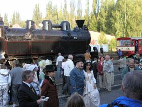 Lidé v kostýmech z 19.století před parní lokomotivou